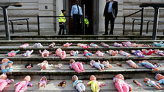 Activists lay dolls at Treasury to protest cuts to Britain's aid budget
